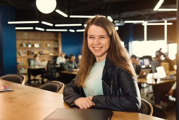 Улыбающаяся женщина-фрилансер, работающая в коворкинге или творческом пространстве, сидит возле ноутбука над группой людей