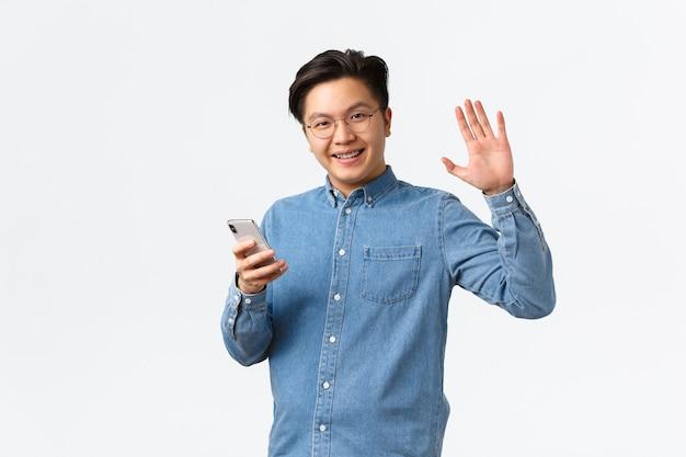 Sorridente uomo asiatico amichevole con bretelle usa il telefono cellulare, guardando la fotocamera e agitando la mano alzata, salutandoti, trovando persone online sull'app di appuntamenti, incontrando amici, in piedi sfondo bianco.
