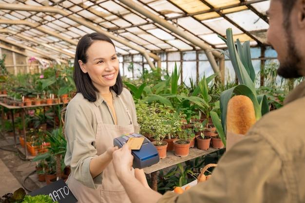 Улыбающийся дружелюбный азиатский продавец держит платежный терминал и благодарит покупателя за покупку в фермерском магазине