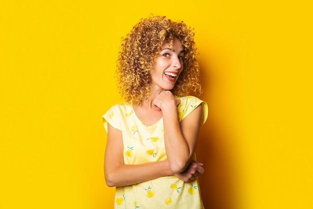 明るい黄色の背景に優しい美しい縮れ毛の若い女性の笑顔