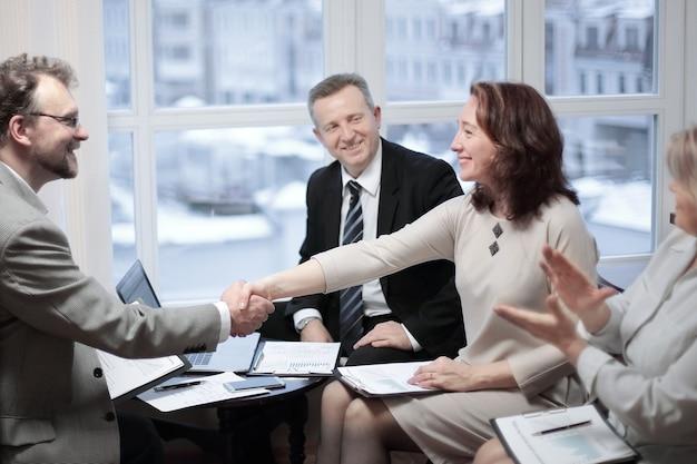 Улыбающийся дружелюбный бизнесмен, пожимая руку женщине, сидящей за офисным столом. концепция партнерства