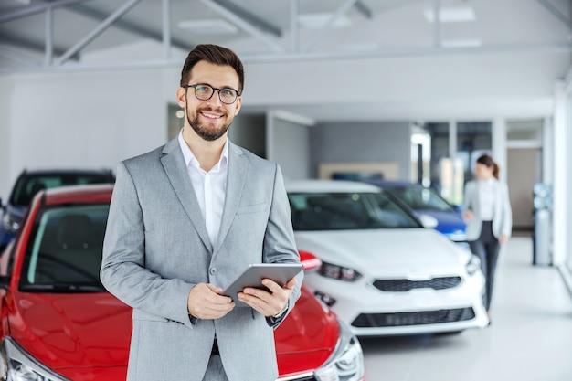 Улыбающийся дружелюбный продавец автомобилей в костюме, стоящий в салоне автомобиля и держащий планшет. всегда приятно купить машину в нужном месте.