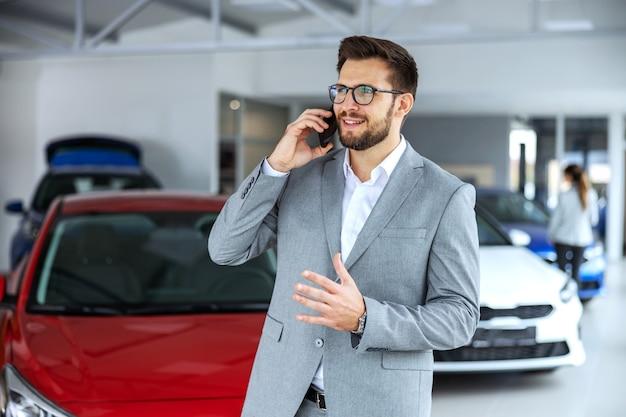 カーサロンに立ってお客様と電話で会話する笑顔でフレンドリーな車の売り手。