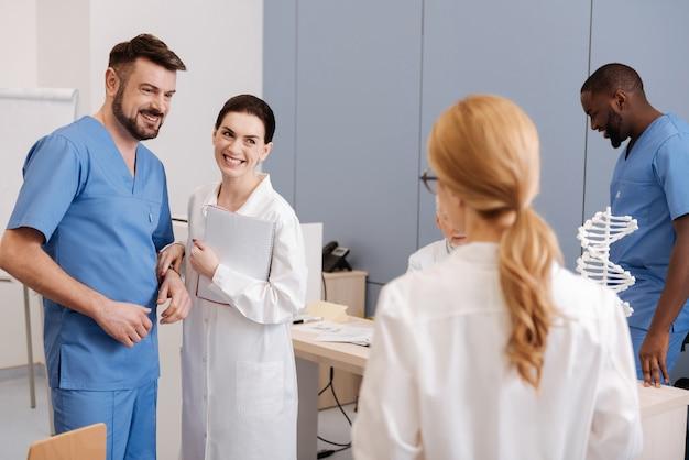 Улыбающиеся дружелюбные опытные врачи изучают и наслаждаются конференцией в клинике, повышая квалификацию и обмениваясь точками зрения.