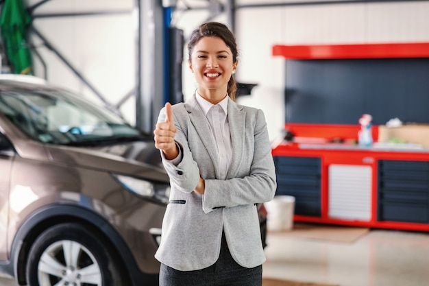 カーサロンのガレージに立って親指を立てて笑顔でフレンドリーな女性の車の売り手。車はすべてセットされ、修理されています。