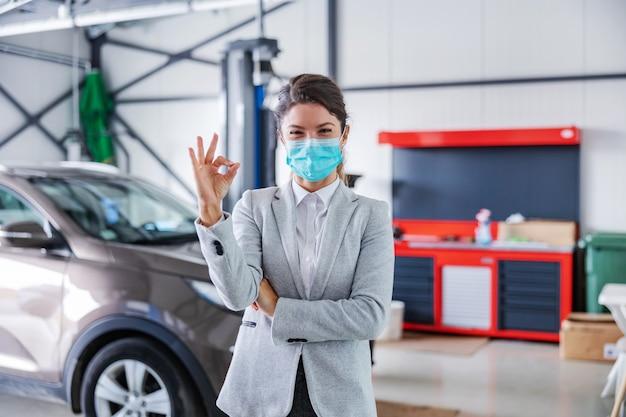 カーサロンのガレージに立ち、大丈夫のサインを見せているフェイスマスクを付けた、笑顔でフレンドリーな女性の車の売り手