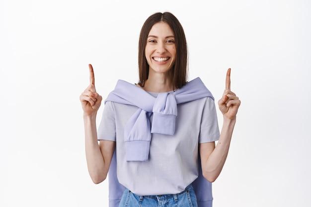Sorridente ragazza amichevole che punta le dita in alto, mostrando il miglior affare promozionale, link per lo shopping o logo webiste, in piedi sul muro bianco