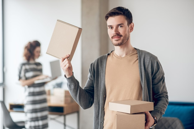 Smiling friendly handsome young dark-haired office employee with cardboard boxes and his busy female colleague with a laptop standing indoors