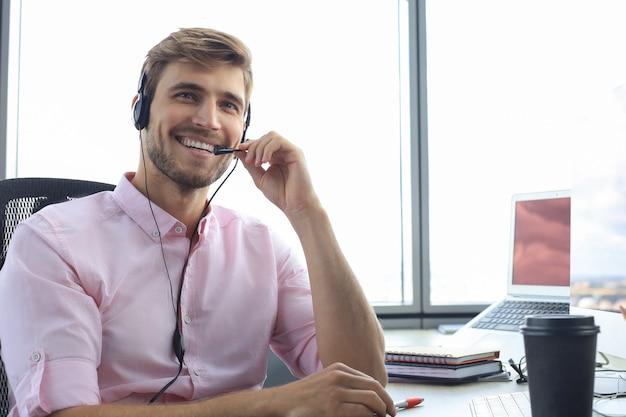 Улыбаясь дружелюбный красивый молодой мужской оператор центра обработки вызовов.