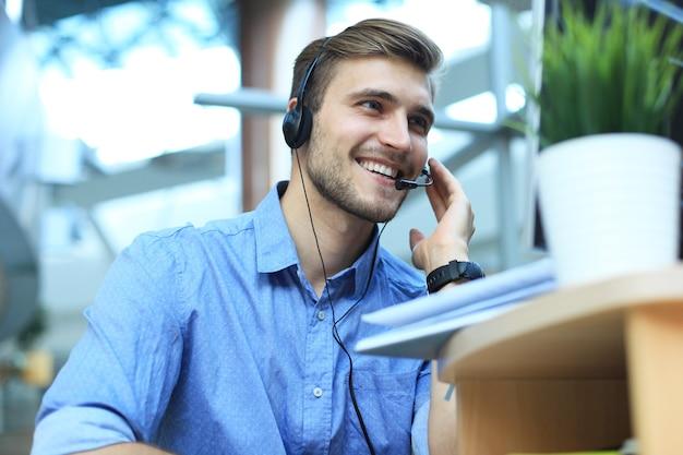 Улыбающийся дружелюбный красивый молодой мужчина оператор call-центра