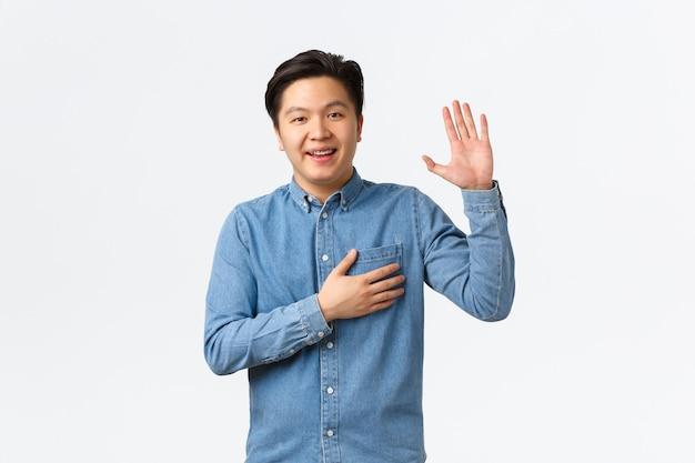 Улыбающийся дружелюбный азиатский мужчина, будучи честным, поднимает руку и держит руку над сердцем, говоря правду, обещая или клянусь чем-то, искренне стоя на белом фоне.