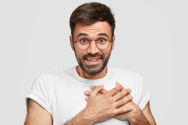 Smiling friendly looking male with stubble, keeps hands on chest, expresses gratitude, has happy expression, wears casual t-shirt, has dark beard, isolated on white wall. acknowledgement concept