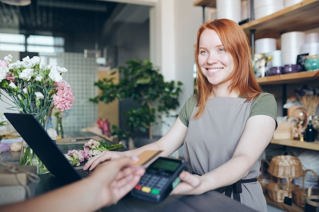 Smiling friendly redhead girl in aprin standing at counter and holding payment terminal for wireless payment while selling flowers in shop