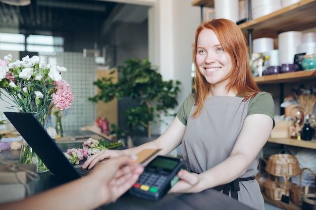 Улыбающаяся дружелюбная рыжая девушка в принте стоит у прилавка и держит платежный терминал для беспроводной оплаты, продавая цветы в магазине