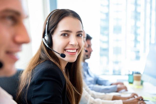 Smiling friendly woman working in call center office with team