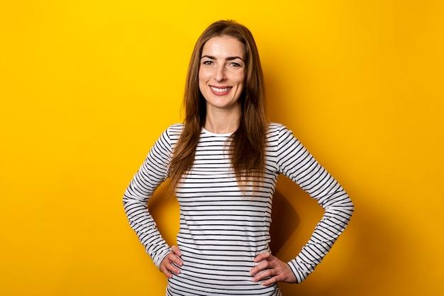 Улыбается дружелюбная молодая женщина в полосатой футболке на желтом.