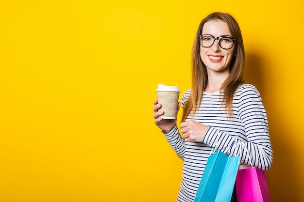 Улыбающаяся дружелюбная молодая женщина радуется, держа бумажный стаканчик с кофе и пакеты на желтом фоне
