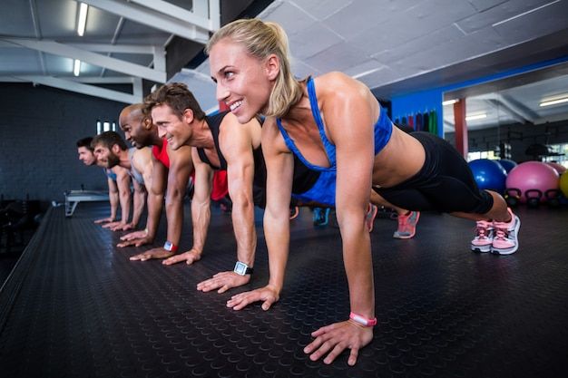 Smiling friends doing push-ups in gym