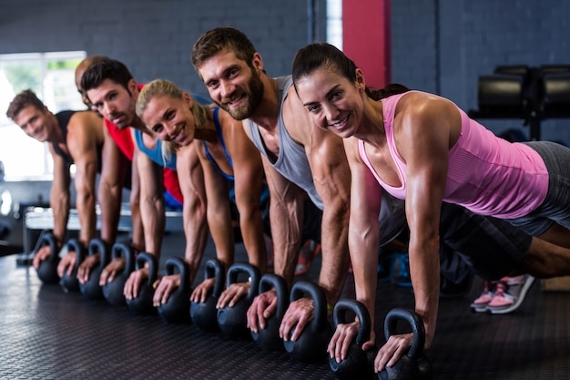Smiling friends doing push-ups with kettlebell in gym