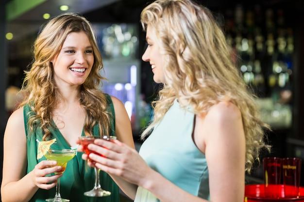Улыбающиеся друзья пьют коктейли