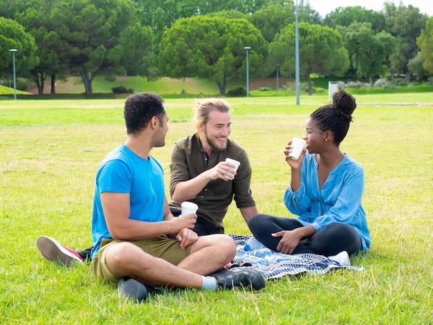Улыбающиеся друзья пьют из бумажных стаканчиков в парке