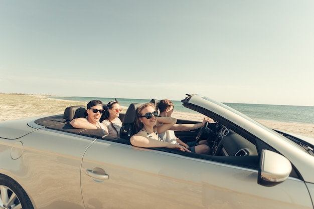 Smiling friends driving car near the sea and having fun
