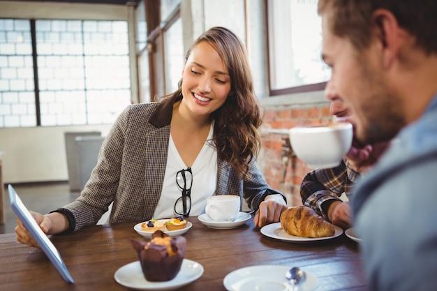 コーヒーを楽しんでタブレットを見る笑顔の友達