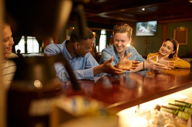Улыбающиеся друзья отдыхают за стойкой в баре. группа людей отдыхает в пабе, ночной образ жизни, дружба, празднование события