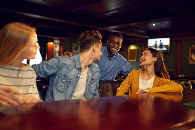 Smiling friends leisures at the counter in bar. group of people relax in pub, night lifestyle, friendship, event celebration