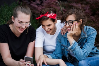 Smiling friends looking at smartphone screen