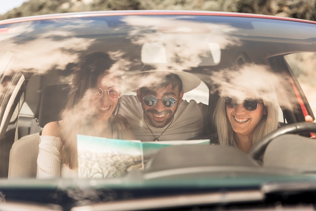 Smiling friends looking at map sitting inside the car
