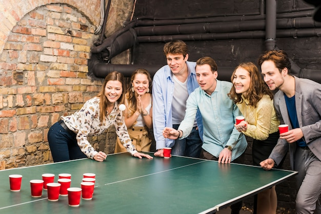 Smiling friends playing beer pong on table in bar