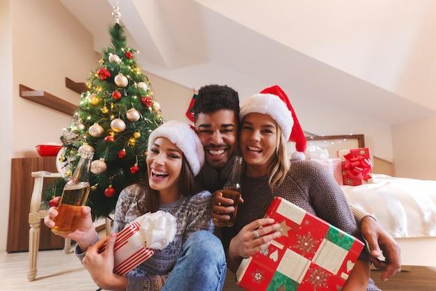 침실에서 손에 선물 및 맥주 병 포즈 웃는 친구. 크리스마스 휴일 개념입니다.