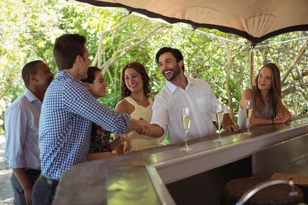 Smiling friends shaking hands at counter