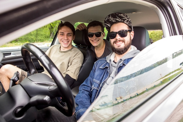Smiling friends sitting in car in travel