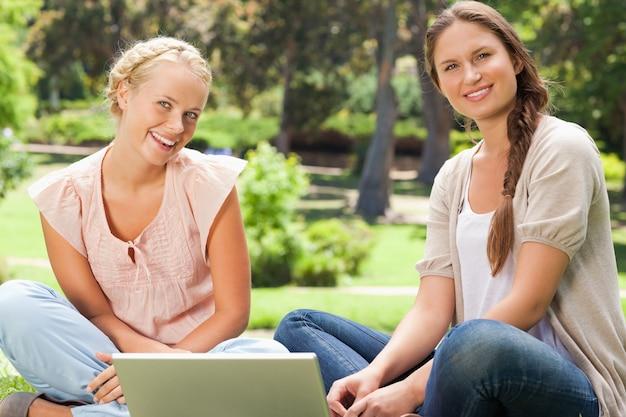 ラップトップで公園に座っている笑顔の友達