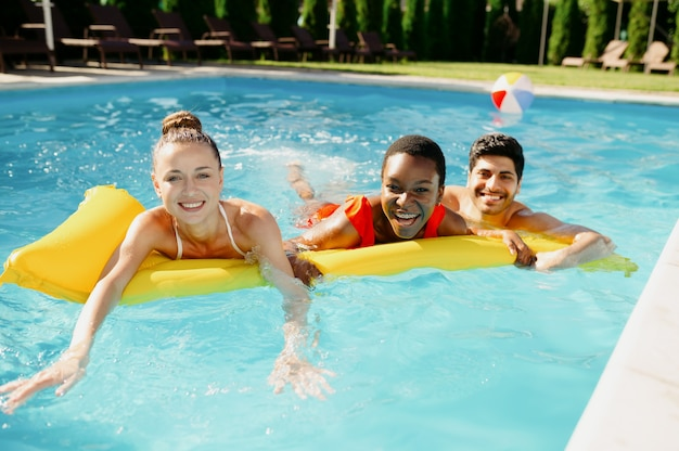 Smiling friends swim on a mattress in the pool