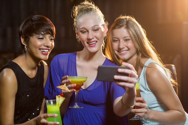 Smiling friends taking a selfie from mobile phone while having cocktail