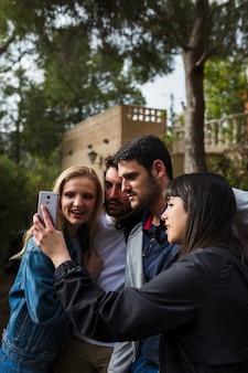 Smiling friends taking selfie in mobile camera
