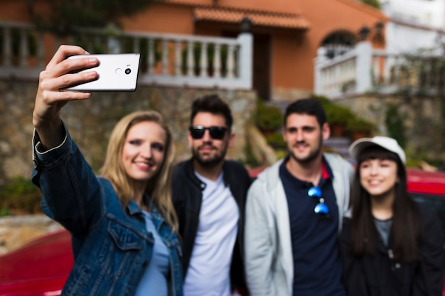 Smiling friends taking selfie with cell phone