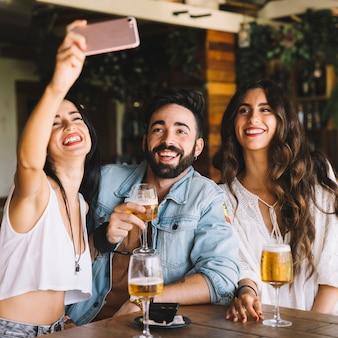 Smiling friends taking selfie Free Photo