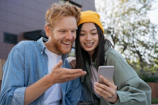 オンラインでビデオショッピングを見ている携帯電話を使用して笑顔の友人