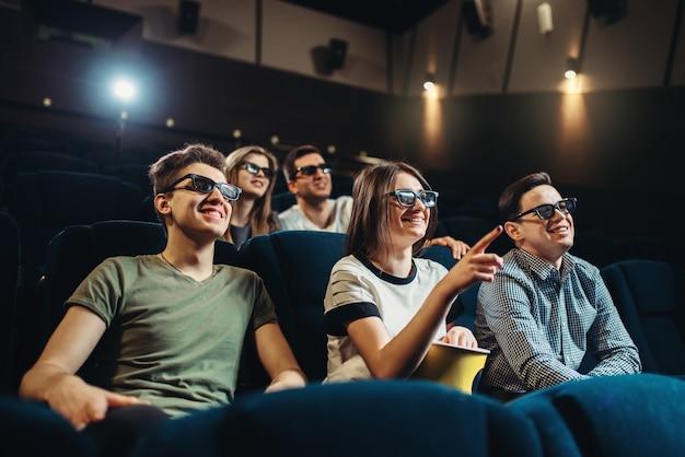 Улыбающиеся друзья смотрят 3d-фильм в кино. showtime, технологии индустрии развлечений