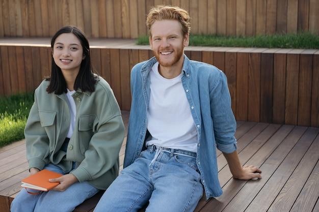 公園で一緒に座ってリラックスしてカジュアルな服を着て笑顔の友人