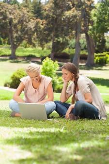 芝生に座ってラップトップを持つ笑顔の友人