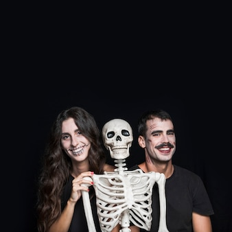 Smiling friends with creepy skeleton