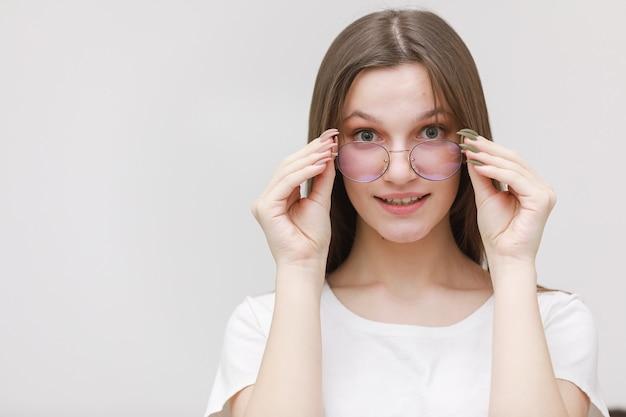 Улыбаясь хмурится офисная девушка, глядя в камеру через очки на белом фоне. молодая женщина, регулируя очки. концепция ношения очков.