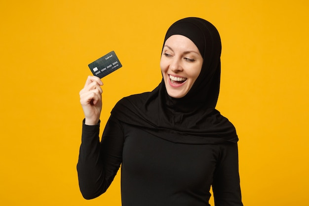 Smiling fun young arabian muslim woman in hijab black clothes hold in hand credit bank card isolated on yellow wall  portrait. people religious lifestyle concept.