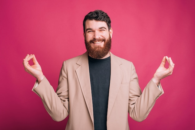 Smiling funny bearded man is trying to make zen gesture with his hands.
