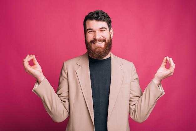 Улыбающийся смешной бородатый человек пытается сделать жестом дзэн своими руками.